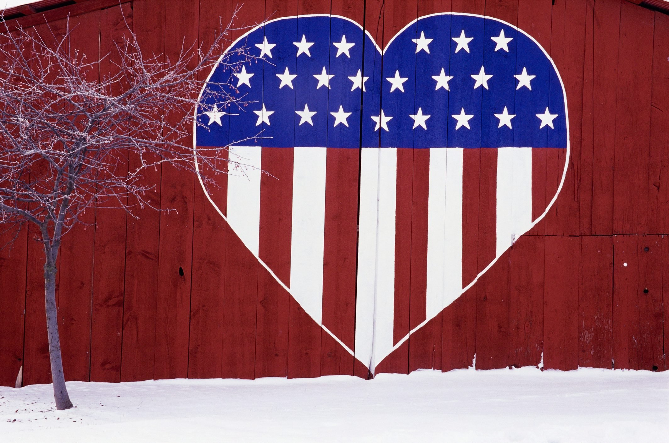 The side of a red barn in Eastern Washington State is decorated with a large heart containing the Stars and Stripes.