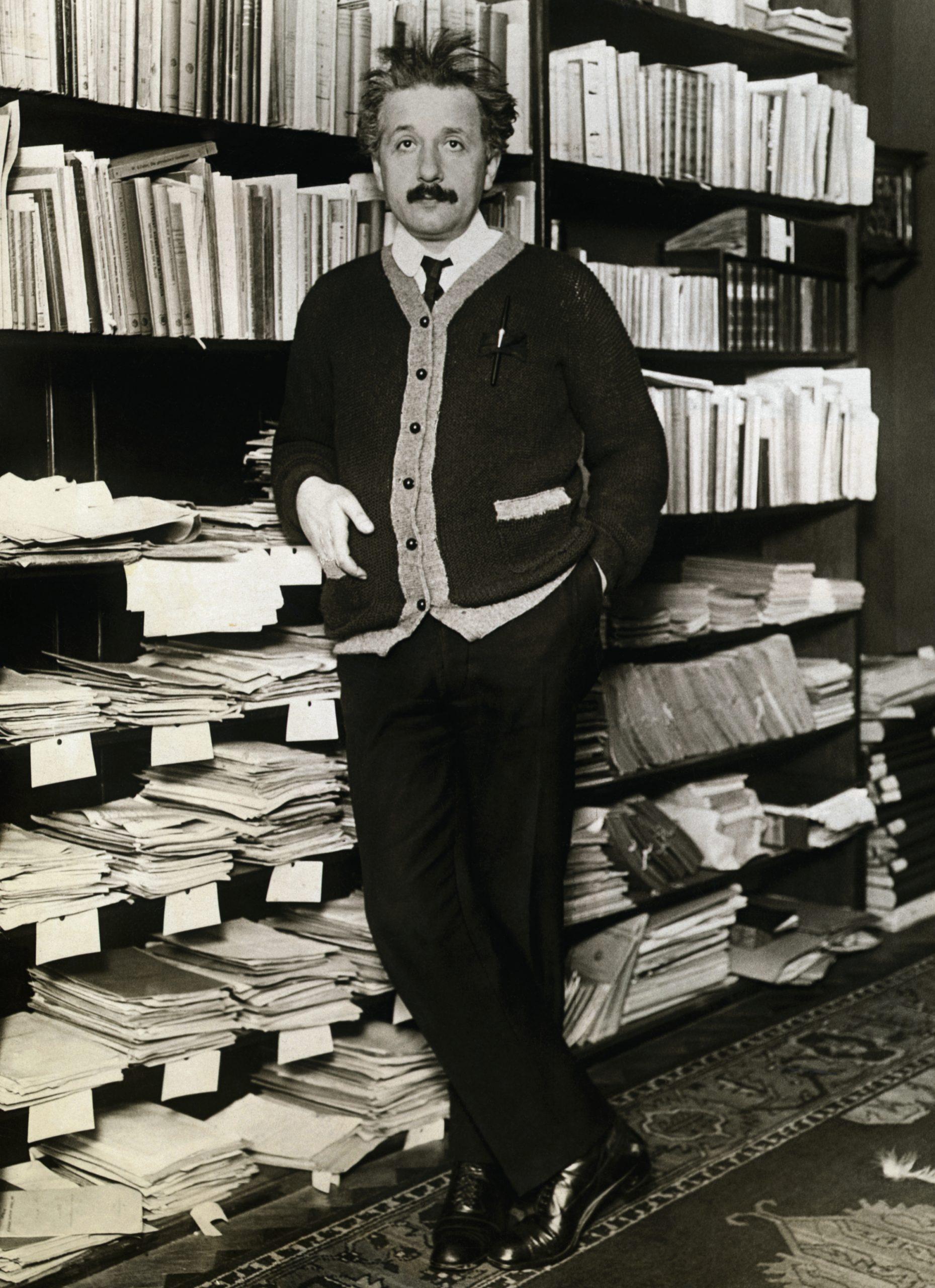 Albert Einstein leaning against shelves of scientific books