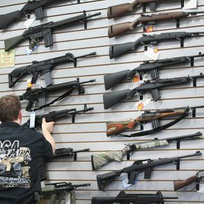 guns displayed on a wall in a store with an anonymous gun salesman