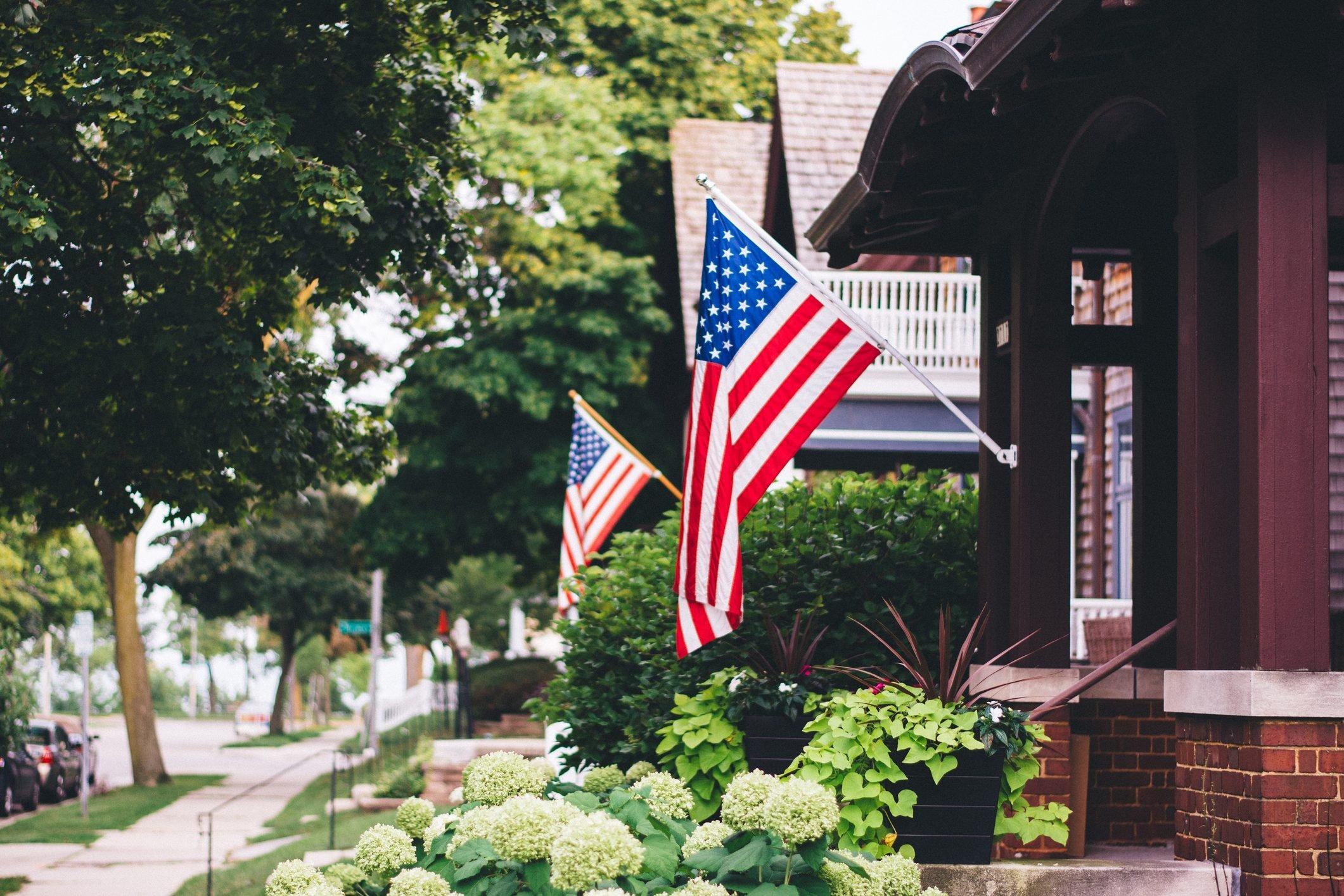 American Flags On consecutive houses along a quaint neighborhood street
