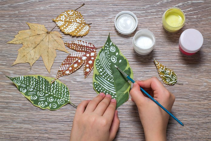 Girl paints patterns of dry autumn leaves