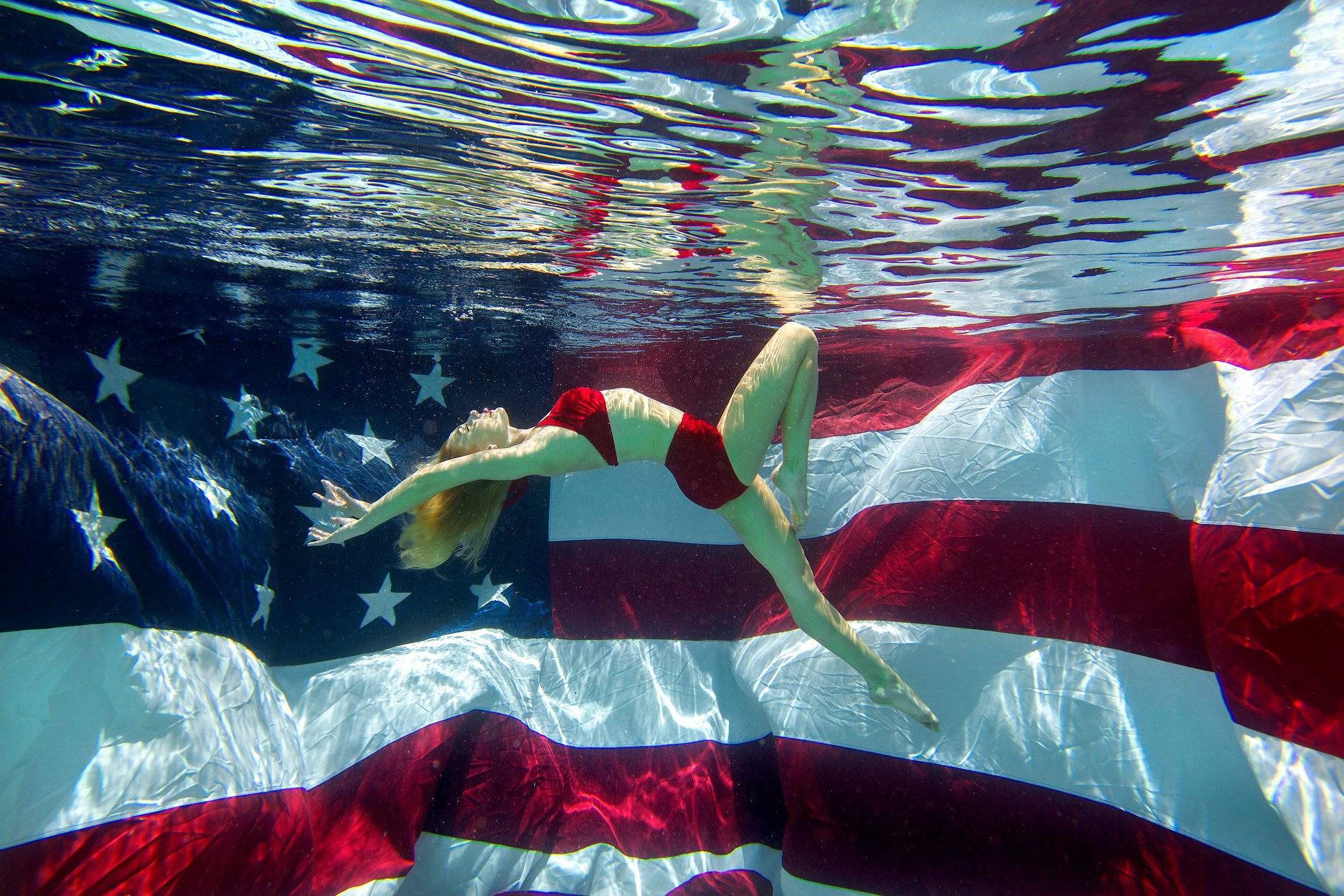Portrait of a woman in a bikini underwater in a swimming pool with an American flag in the background in San Diego, California.