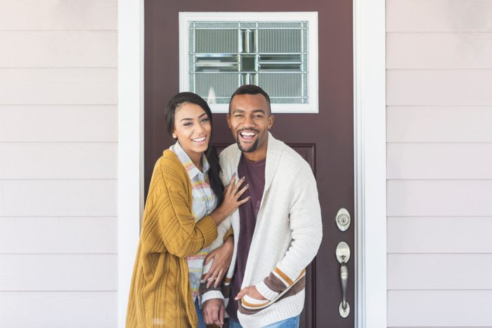 Young mixed race couple standing by front door