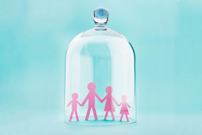 Family silhouette protected under a glass dome on blue background
