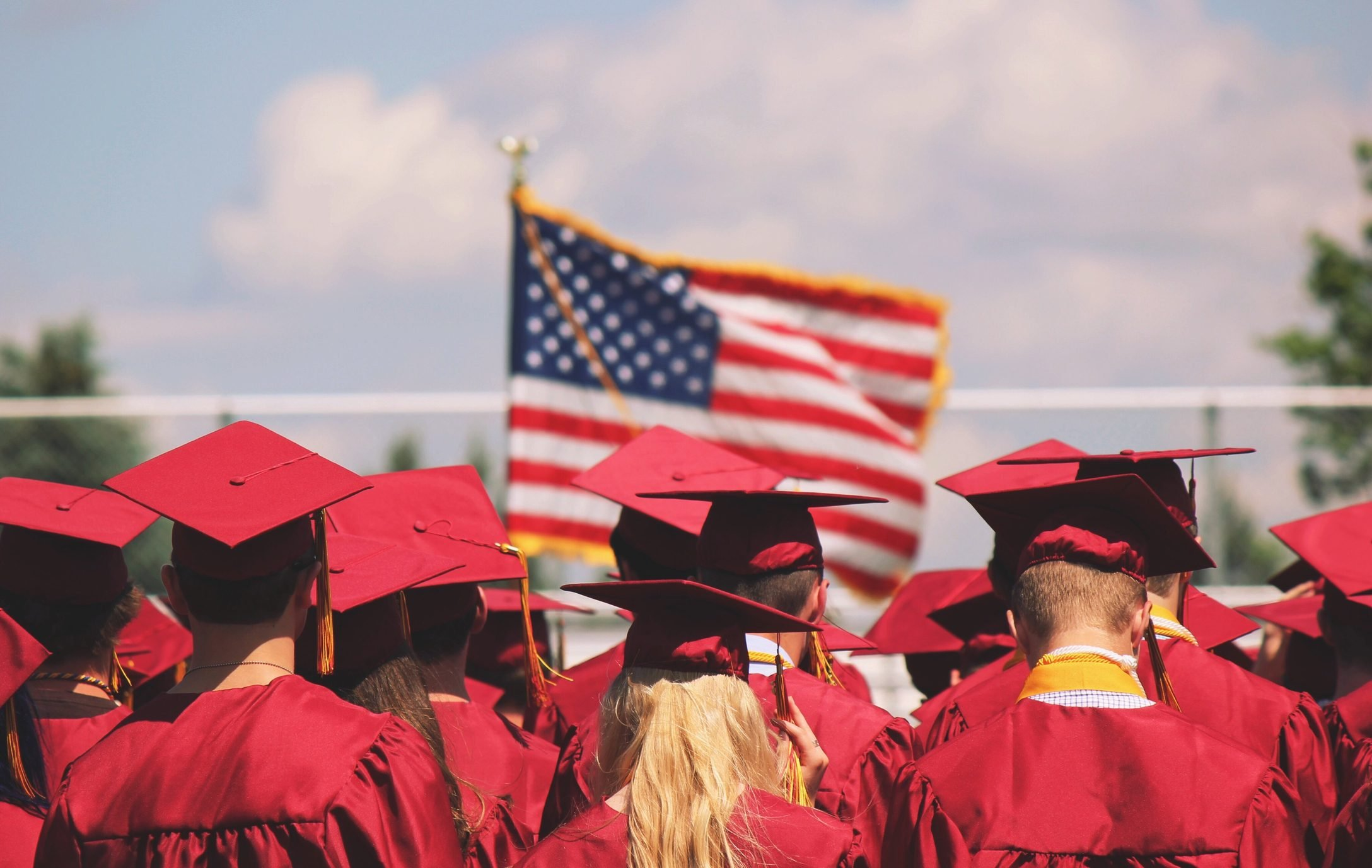 Rear View Of Graduates Standing Outside On A Sunny Day With An American Flag In The Background