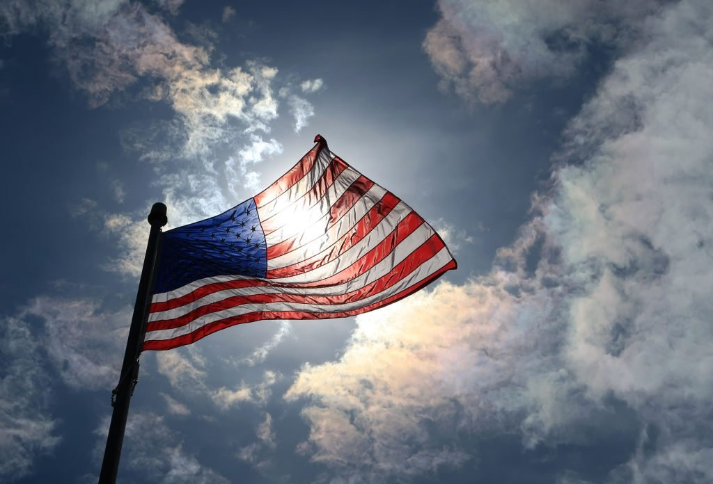 an upward view of the sun streaming through a wavy american flag against they sky in atlantic highlands, new jersey