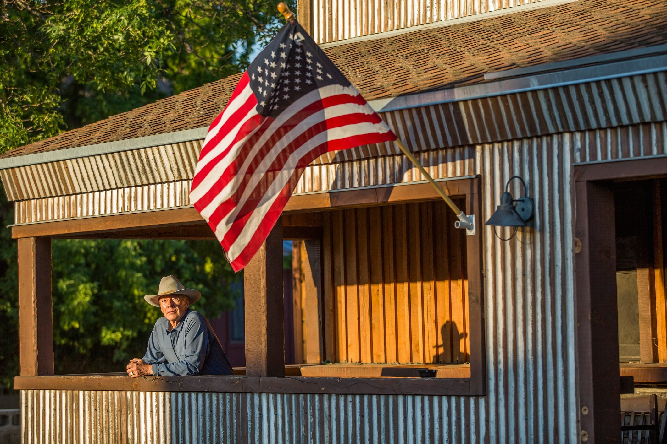 Serious farmer on his porch with an American flag in low, golden sunlight