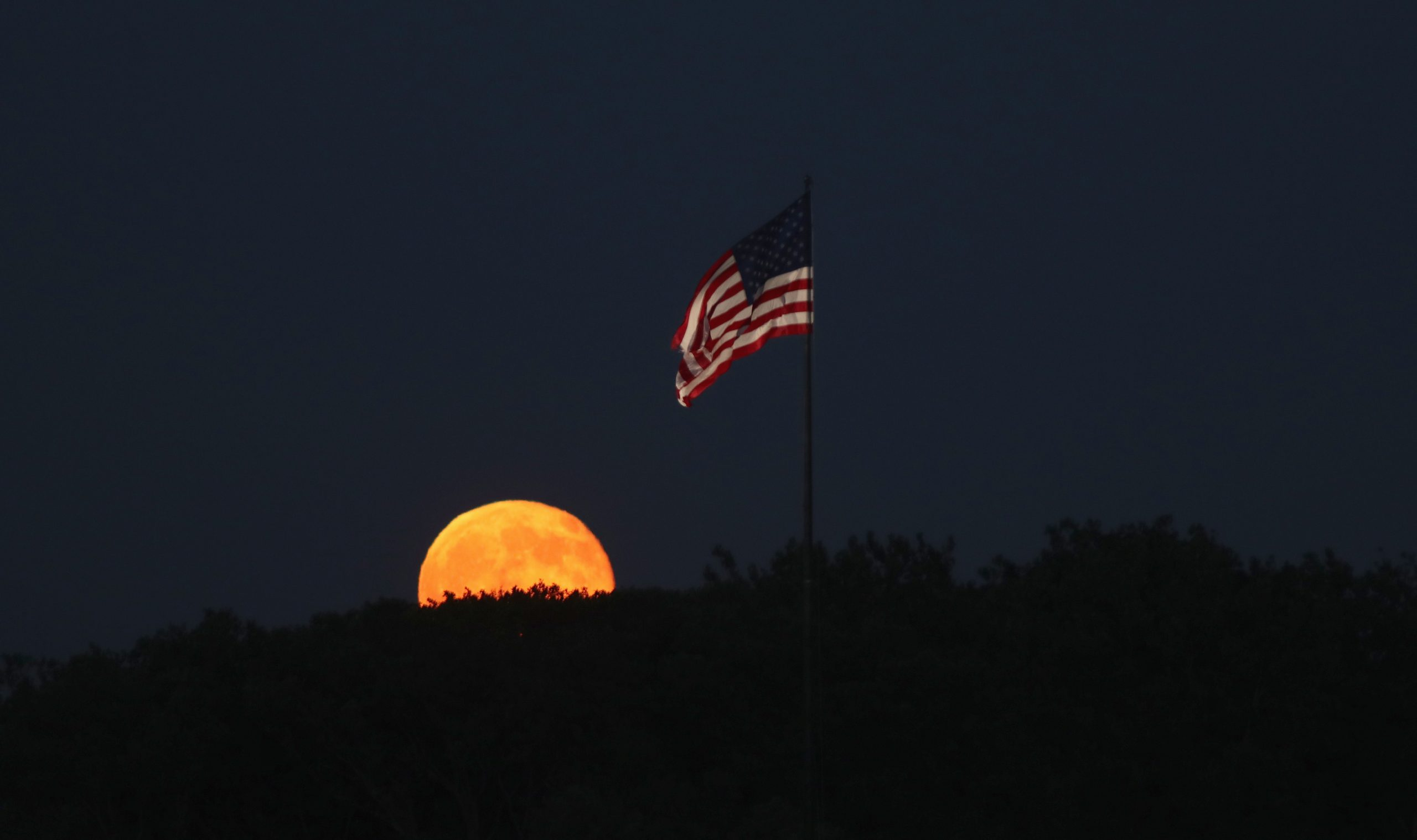 The moon rises behind a flag on Liberty Island in New York City on July 9, 2017 as seen from Jersey City, New Jersey.