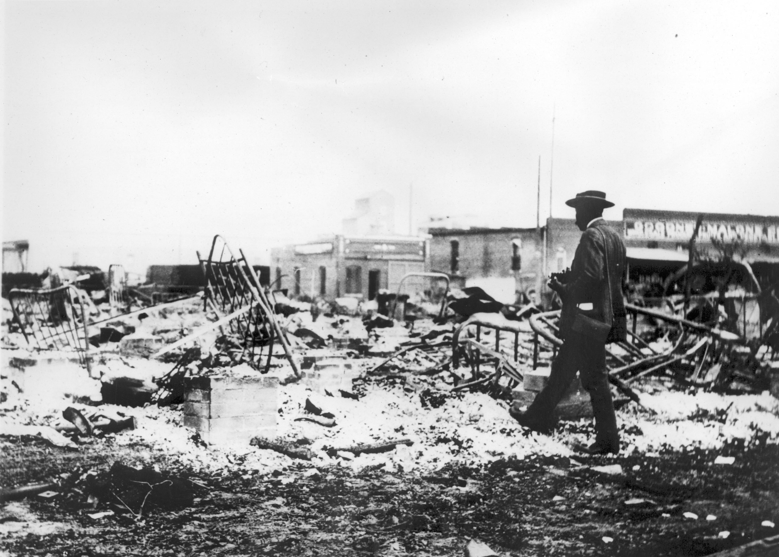 An African-American man with a camera looking at the skeletons of iron beds after the Tulsa Race Massacre
