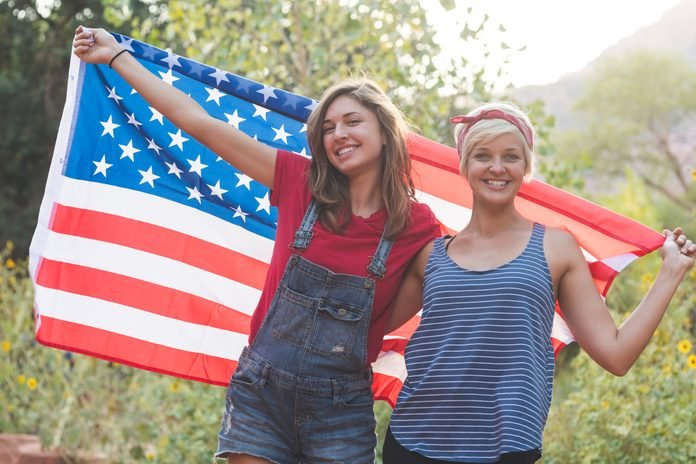Two friends drape themselves in an American flag outside
