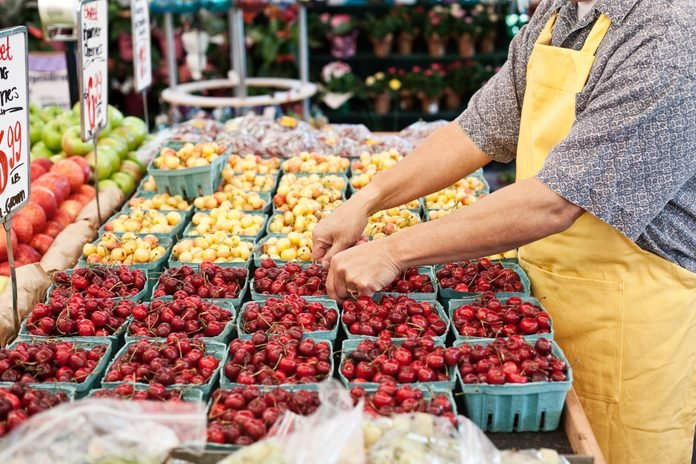 Man wearing apron standing at stall with punnets of fresh cherries at a fruit and vegetable market.