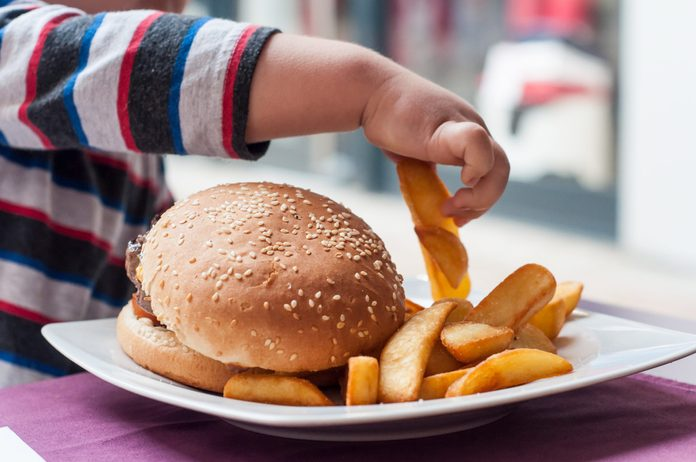 little boy hand eating hamburger and french fries at restaurant