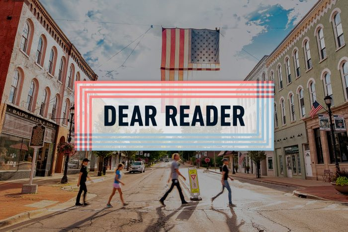 """""""Dear Reader"""" logo over main street buchanan, MI with people crossing the road and a large american flag overhead"""