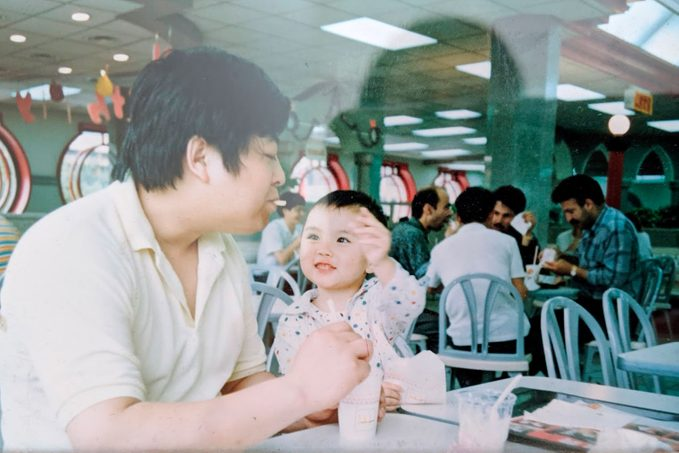 the author, C Pam Zhang, as a young child with her father in a fast food restaurant