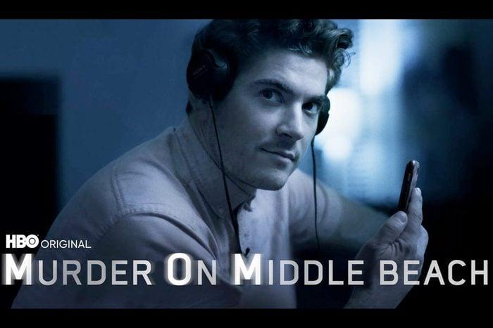 Man wearing Sony headphones holding phone
