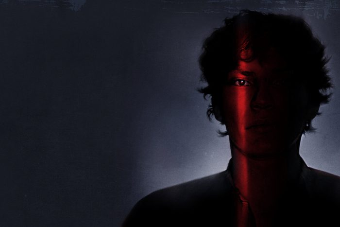 Man in shadows with slit of light highlighting eye