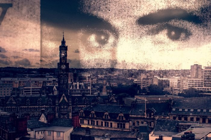 Man's eyes overlayed on a landscape view of a city