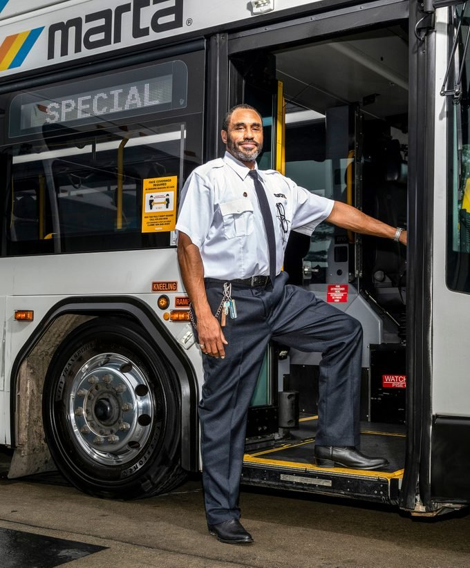 Winston Douglas standing outside the bus he drives