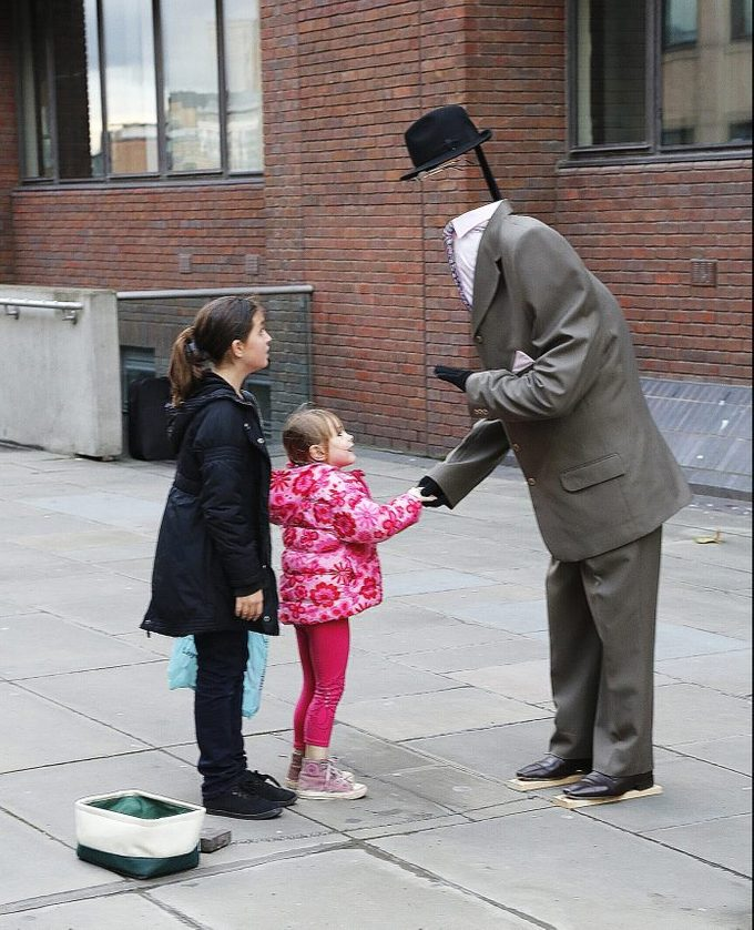 two young girls stand near a seemingly headless street performer