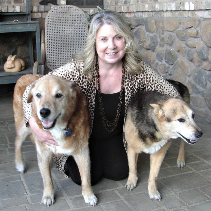 Sharon Scott kneeling with her two dogs