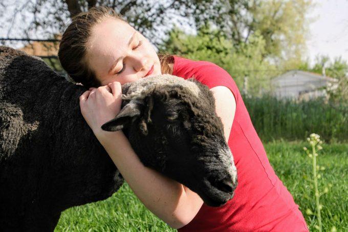 Grace hugs her goat, Esther
