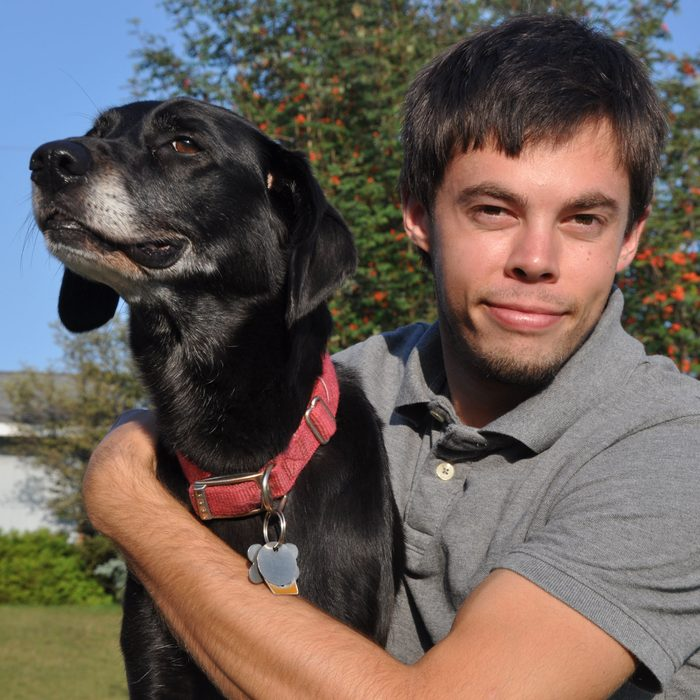 a young man sits with his arm around a black dog