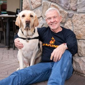 a veteran and his service dog sit together