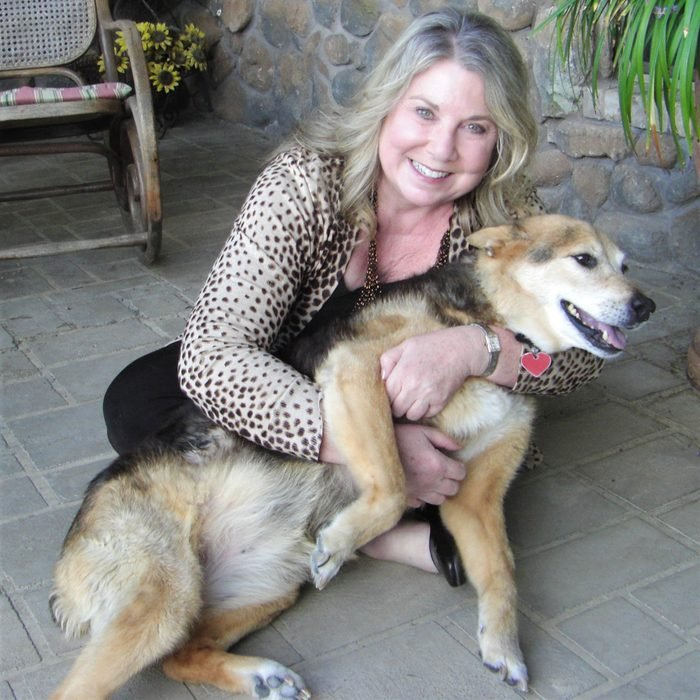 woman sits on the ground holding and petting dog in her lap