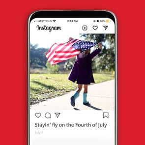 iPhone with Instagram app displaying photo of young girl flying American flag