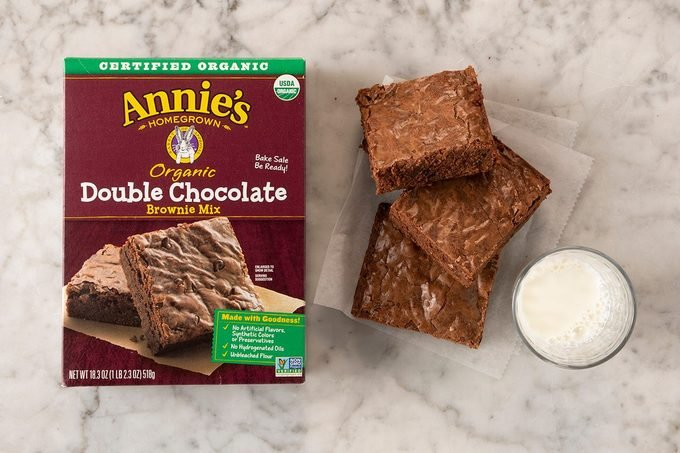 Annie's Organic Double Chocolate Brownie Mix in package on marble with pieces and milk