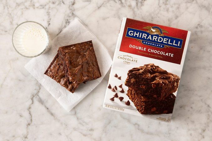 Ghiradelli Double Chocolate Brownie Mix in package on marble with pieces and milk