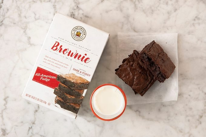 King Arthur All-American Fudge Brownie Mix in package on marble with pieces and milk