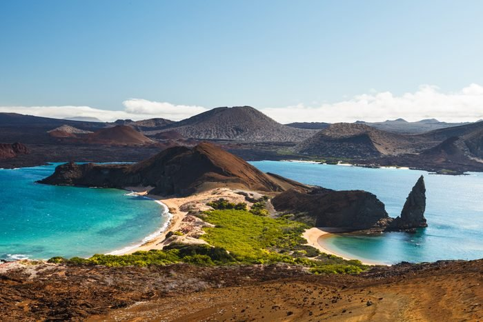 View on the volcanic landscape of Bartolome Island with famous Pinnacle Rock and Golden Beach in the Galápagos Islands, Ecuador