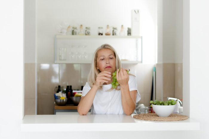 Woman standing in kitchen and eating grapes