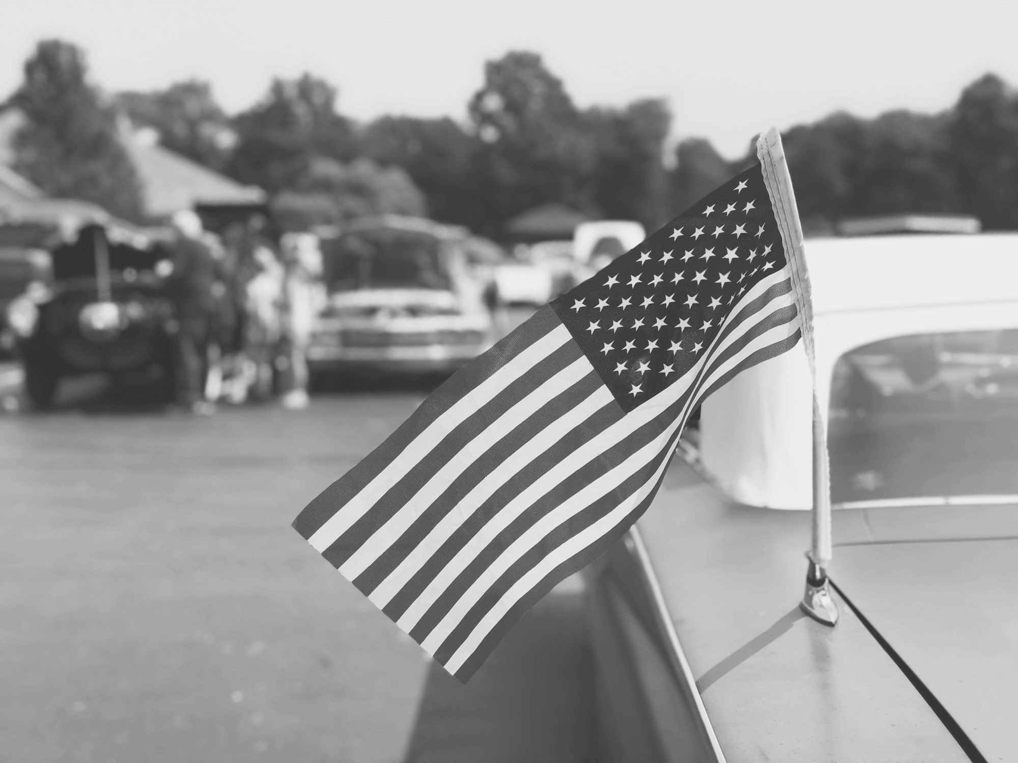 black and white image of an American Flag on an Old Classic Car at a Car Show