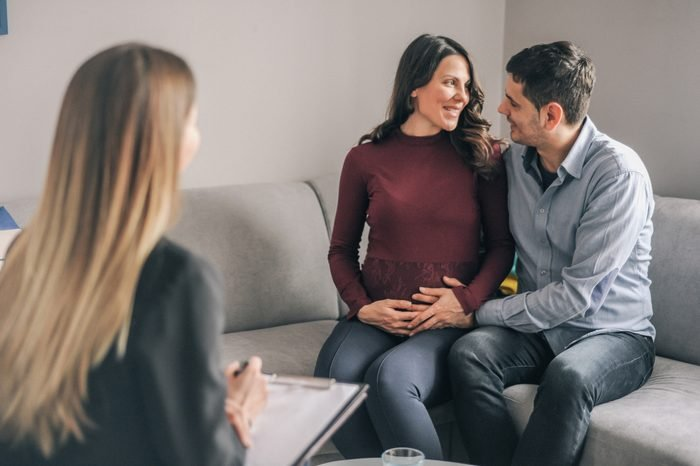 Genetic counseling consultant advising couple during pregnancy