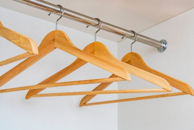 Wooden hangers on a rod in an empty closet