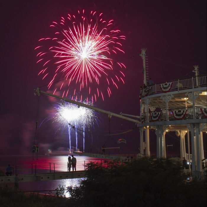 A couple watches fireworks from the walkway of a riveboat.