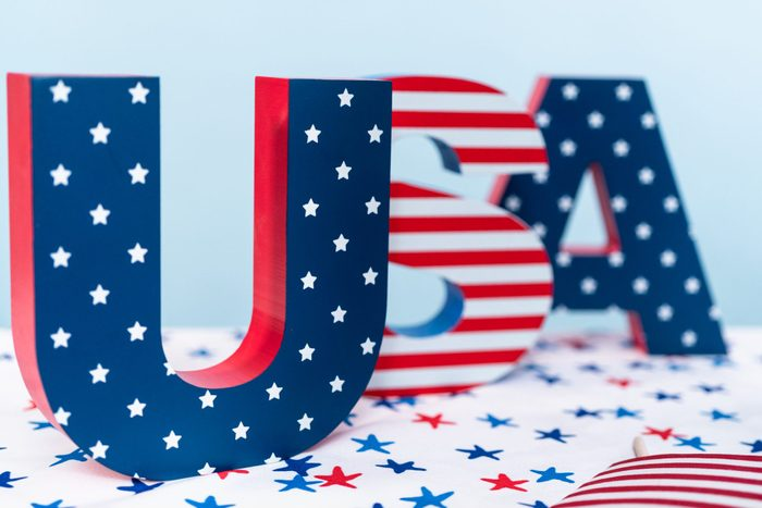 Red, white, and blue USA sign decorated with stripes and stars.