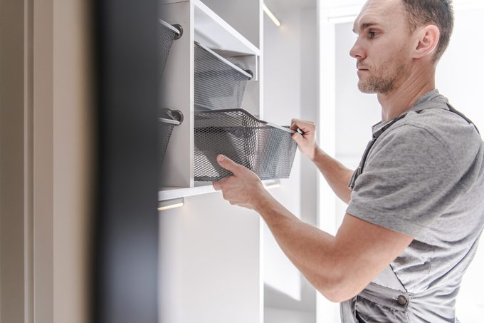 man adding shelves and baskets for organization to a newly remodeled closet