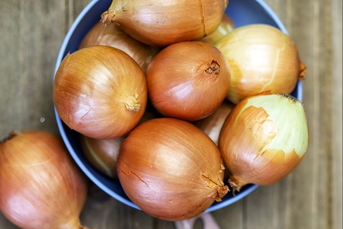 A Group Of Organic Yellow Onions In A Blue Bowl On A Wooden Cutting Board