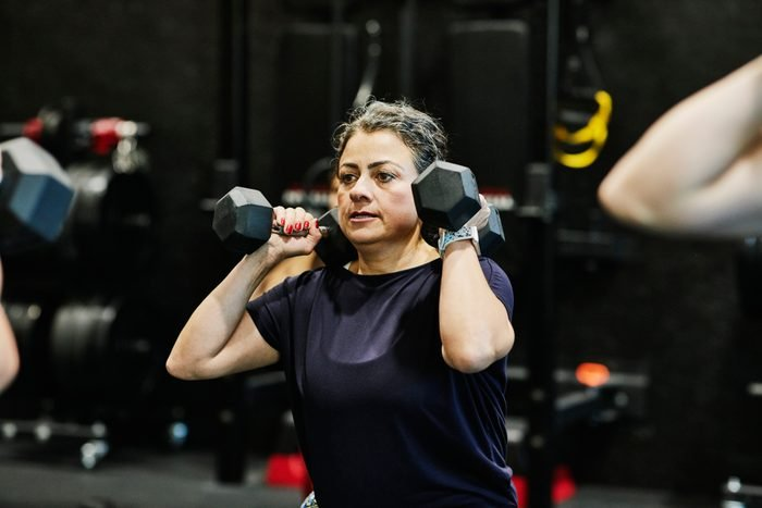 Woman doing dumbbell squats during fitness class in gym