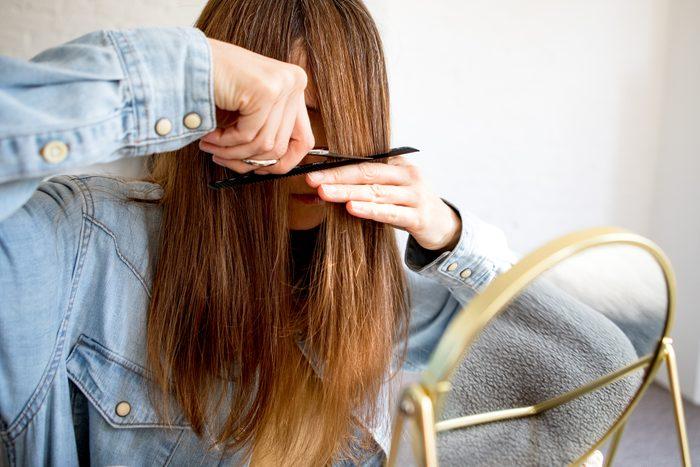 A woman cutting her own hair