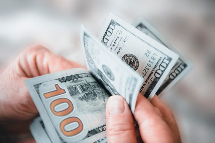 Close-up shot of an unrecognizable senior adult holding Dollar banknotes