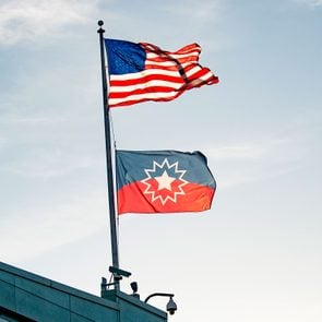 the american flag and the juneteenth flag wave atop a building with the early evening sky background