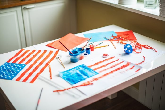 kids craft table with paints and paper and drawings of the american flag