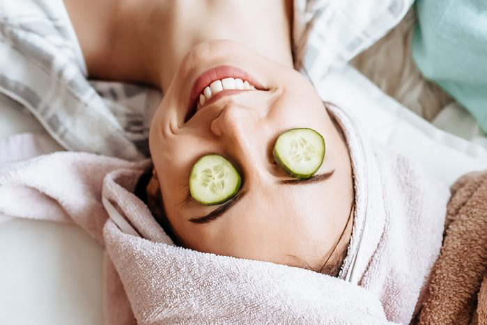 Two girls make homemade face and hair beauty masks. Cucumbers for the freshness of the skin around the eyes. Women take care of youthful skin. Girlfriends laugh at home lying on the floor on pillows.
