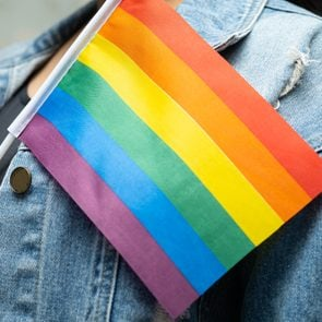 anonymous lgbtq ally wearing denim jacket and holding rainbow pride flag
