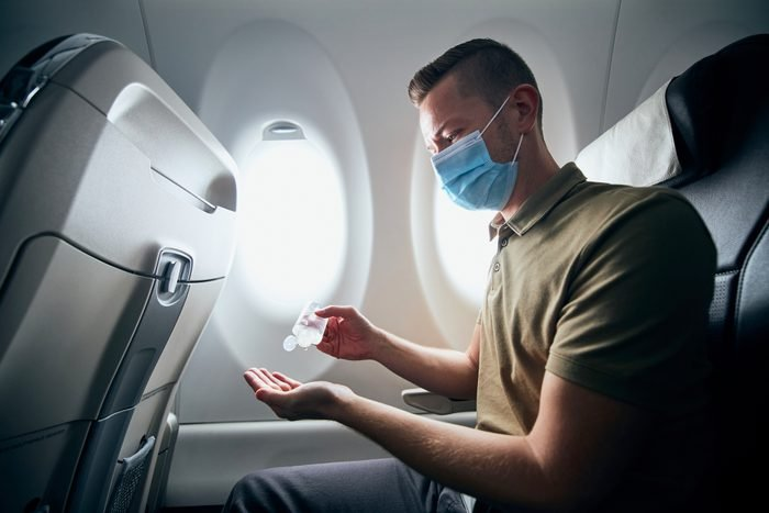 Man wearing face mask and using hand sanitizer inside an airplane