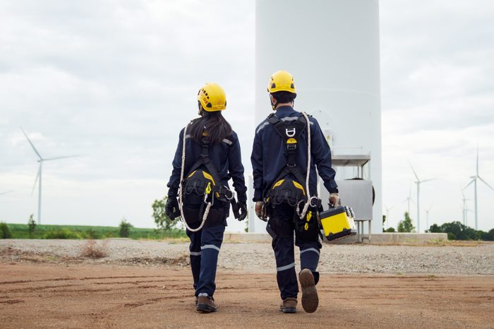 Two Electric engineer wearing Personal protective equipment working in wind turbine farm.
